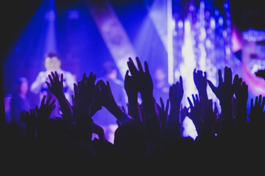 Musikkonzert: Menschen strecken ihre Hände in die Höhe, feiern und genießen die Musik.