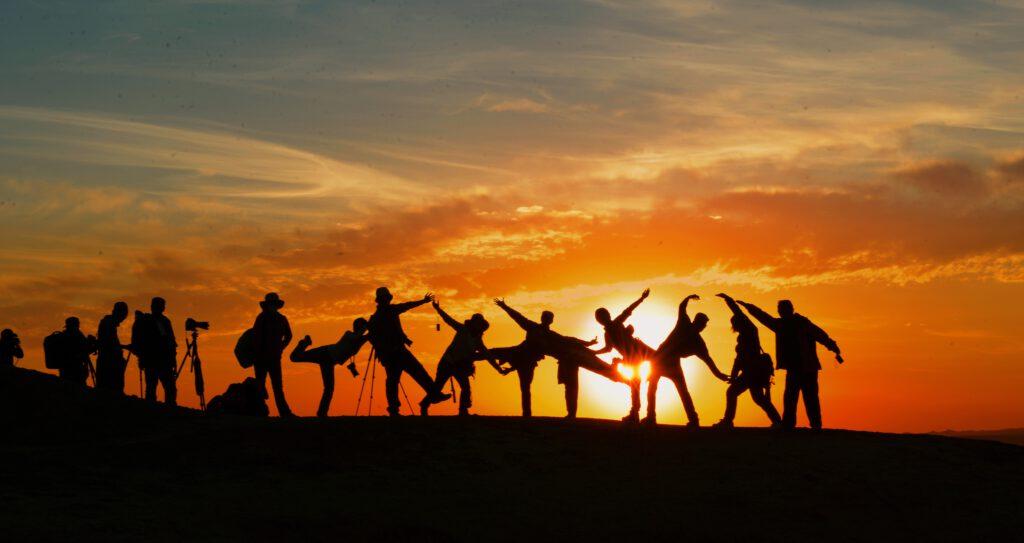 Tanzende Menschen im Sonnenuntergang als Ausdruck von Freude, die im Coaching gefunden werden kann.